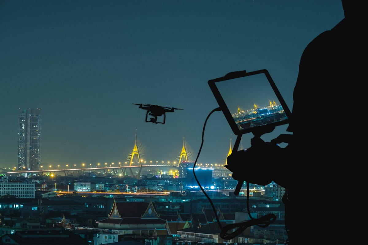 Silhouette of Man using drone to monitor the city at night.